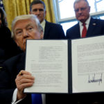 President Donald Trump holds an executive order dealing with the structure of the National Security Council after signing it in the Oval Office at the White House on January 28, 2017.