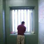 A young man looks out a cell window while serving a sentence for burglary in Waldo County.