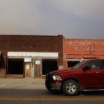 A man drives his truck past shuttered storefronts on the main street of Buffalo, Oklahoma.