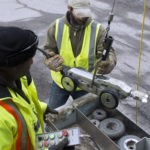 BANGOR, Maine -- 042114 -- City workers Tony Young [left] and Jeremy Linscott pull from a manhole the remote controlled camera that they use to assess sewer lines on Friday. Nick Sambides Jr. | BDN