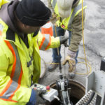 City workers Tony Young [left] and Jeremy Linscott pull from a manhole the remote controlled camera that they use to assess sewer lines on Friday.
