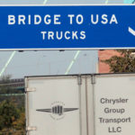A commercial automotive supplier truck passes under a sign leading to the Ambassador bridge crossing over to Detroit, Michigan, from Windsor, Ontario, Sept. 28, 2013.