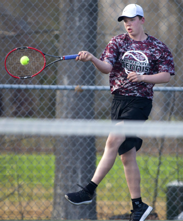 Bangor number one singles Dennis Stewart jumps to return the ball to Brunswick's Dasol Kim during their tennis match at Bangor Friday.