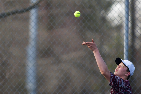 Bangor number one singles Dennis Stewart serves to Brunswick's Dasol Kim during their tennis match at Bangor Friday.