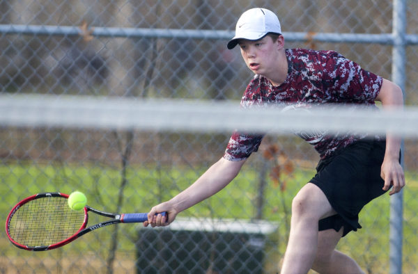 Bangor number one singles Dennis Stewart stretches to return the ball to Brunswick's Dasol Kim during their tennis match at Bangor Friday.