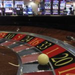 A ball is seen on a roulette wheel in front of slot machines at Gaming Expo Asia in Macau, May 22, 2012.