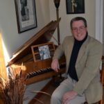 Aaron Robinson sits at his harpsichord in his Alna home on April 14. The harpsichord has a picture of Leonard Bernstein on it.