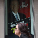 A woman walks by a sign showing Fox News Channel TV anchor Bill O'Reilly outside the News Corporation headquarters in New York City, in New York, U.S. April 19, 2017.