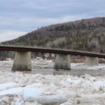 Open water flows under the St. John River bridge in Allagash after the ice jam there broke up in 2015.