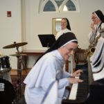 Sisters Miriam Holzman, piano, Louis Marie Zogg, right, saxophone, and Mary Andre Thelen, second from right, trumpet, and Brother Brad Elliott, left, drums, practice with their band Force of Habit for an upcoming concert at Catholic University in Washington.