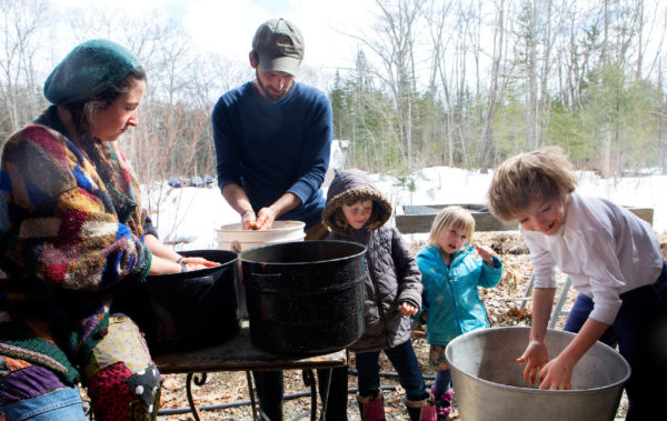 Leah Byers (center), 7,and Liza Byers (second from right), 4, watch as Walden Merkel Cutting (right), 7 agitates a bucket of acorns to remove the skins with Molly Katz-Christy (left) and Steve Byers at their home in Belfast on Thursday. The group expects to make around 20 pounds of acorn flour when they are done.