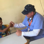 Newman Civic Fellow Duane Belanger brings a smile to a young patient in Brazil by teaching him to thumb-wrestle.