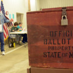 A man emerges from a voting booth in Patten.