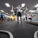 BDN assistant sports editor Pete Warner holds heavy ropes while doing jumping jacks during a recent workout session at Wilcox Wellness and Fitness in Bangor.