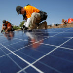 Vivint Solar technicians install solar panels on the roof of a house in Mission Viejo, California, Oct. 25, 2013.