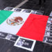 A portrait of murdered journalist Javier Valdez is seen as a woman places photos of other journalists next to the national Mexican flag, during a demonstration against the killing of journalists in Mexico and to demand justice for the 43 missing students of Ayotzinapa Rural Teachers' College outside Argentina's Foreign Ministry in Buenos Aires, Argentina, May 24, 2017.