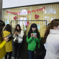 Teachers and students from Harbin, China, check their phones while on a tour of Bangor City Hall, Jan. 30, 2015.