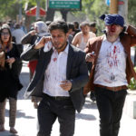 Injured Afghans run from the site of a blast in Kabul, Afghanistan, May 31, 2017.