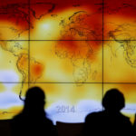 Participants are seen in silhouette as they look at a screen showing a world map with climate anomalies during the World Climate Change Conference 2015 (COP21) at Le Bourget, near Paris, France, Dec. 8, 2015.