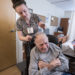 Salena Sawtelle, a certified nursing assistant, combs Ora Bartlet's hair before taking him to breakfast at the Stillwater Health Care facility in Bangor in March.