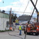 Workers move a downed power line near Preble and Oxford Street Wednesday, after a tractor-trailer struck a telephone pole knocking out power to part of downtown Portland.