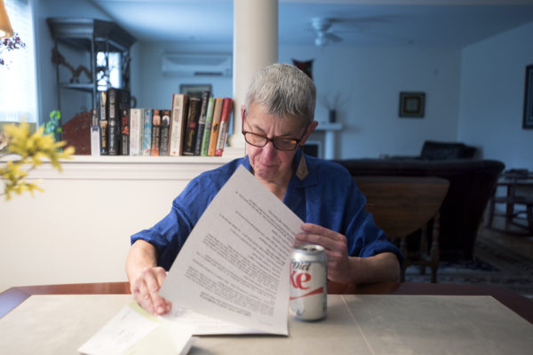Ann Leffler looks through notes while talking about how she has been caring for her spouse, Dair Gillespie, at their home in Orono. Gillespie, who has advanced Alzheimer's disease, is among the first Mainers to be certified to use marijuana to treat the symptoms of Alzheimer's.