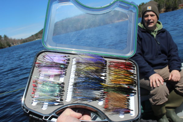 Rob Dunnett steers the boat as a fishing partner checks out a box of streamer flies that Dunnett tied.
