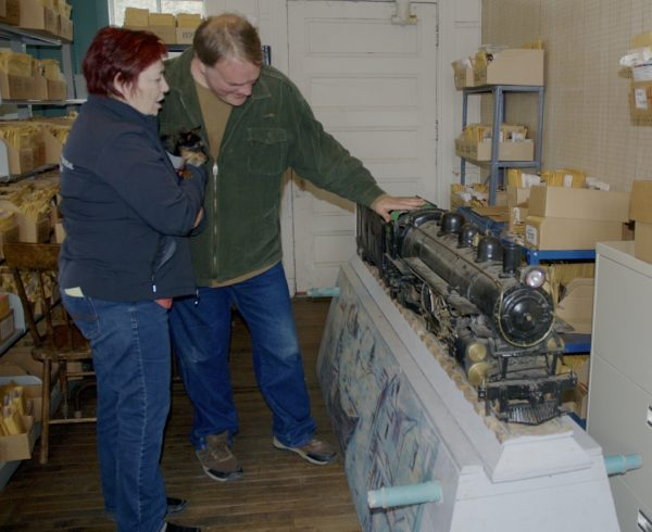 Chad Pelletier, president of the Fort Kent Historical Society, and Lise Pelletier, director of the Acadian Archives in Fort Kent, look over the scale model train built by a local fabricator in the early 1960s and recently donated to the historical society.