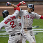 Boston's Mookie Betts (right) celebrates with teammate Xander Bogaerts (2) after hitting a three-run homer in the ninth inning against the Milwaukee Brewers at Miller Park on Thursday.