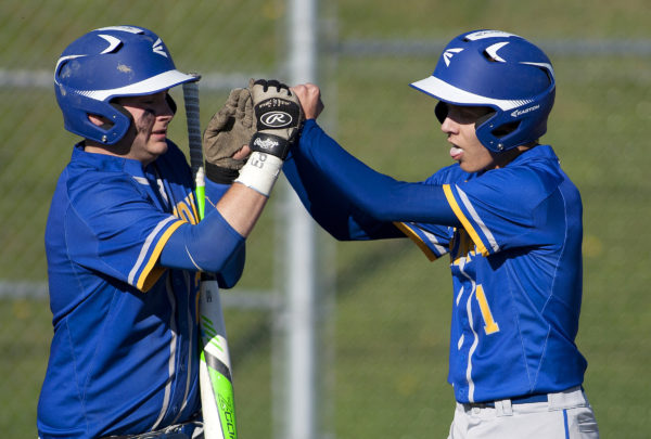 Hermon's Alex Applebee (right) celebrates with teammate Christian Greener after scoring a run against Ellsworth during their baseball game in Hermon Friday.