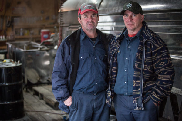 Benoit (left) and Alcide Giroux stand inside their sugar house in Big Six Township on Monday. Their grandfather first made maple syrup on the land in the 1940s.