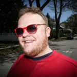 "Portland comedian Connor McGrath stands on the leafy street in Deering he's called home for most of his life. McGrath's Asperger's syndrome doesn't hinder his comedy, he said, ""It's just like being left handed."" Troy R. Bennett 