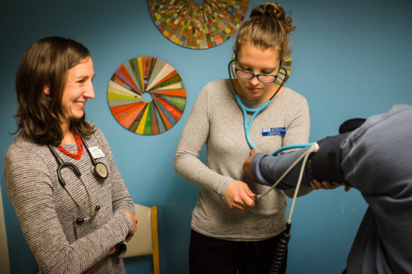 Nursing student Courtney Wilson checks a patient's blood pressure under the watchful eye of nurse practitioner Gretchen Speed at the Greater Portland Health clinic on May 9.  Wilson is graduating this month from the University of New England's accelerated nursing program.