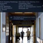 Eastern Maine Medical Center staff walk down a hallway in the hospital in Bangor.