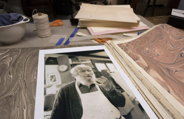 A photograph of Peter Werner's grandfather, Arno Werner, and hand-decorated paper the two made together years ago. Werner is a master bookbinder who learned the craft from his grandfather.