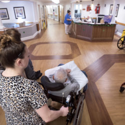 Salena Sawtelle pushes Ora Bartlet to the dining hall before breakfast at the Stillwater Health Care facility in Bangor recently.