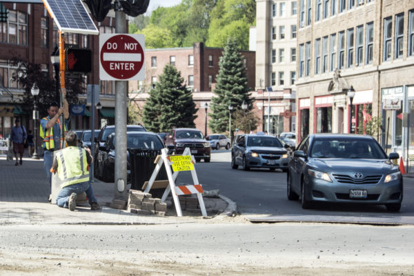 City workers set up a temporary crosswalk sign at Hammond and Central streets in downtown Bangor on Thursday. Businesses there say construction work being done is hampering some sales, but that it's necessary.