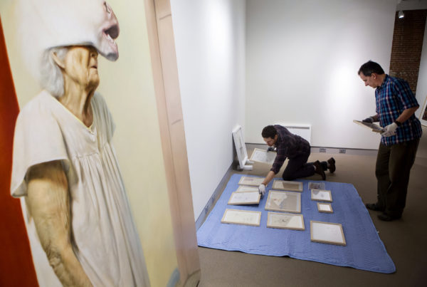 Shawn Lefevre (left) and Aaron Pyle work to install the work of New York-based artist Jason Bard Yarmosky at the University of Maine Museum of Art in Bangor Thursday. Yarmosky's show features large, realistic paintings of his elderly grandmother, who is diagnosed with Alzheimer's disease.