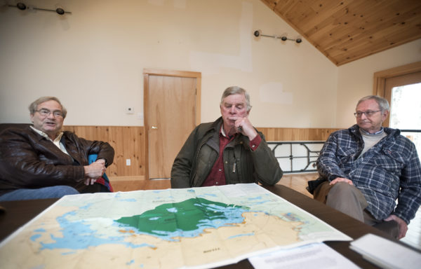 David Townsend, cottage owner in Forest City, New Brunswick (from left), Dale Wheaton, former owner of Wheaton's Lodge in Forest City, Maine, and Blaine Higgs, member of New Brunswick legislature who owns a cottage in Forest City, New Brunswick, talk about concerns surrounding the dam on East Grand Lake.