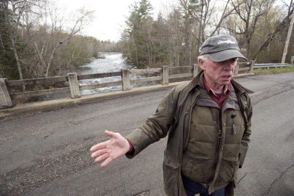 Dale Wheaton, former owner of Wheaton's Lodge in Forest City, Maine, on the bridge over the  Forest City Stream at the border crossing between the United States and Canada.  The owner of the Forest City dam, Woodland Pulp LLC., filed papers to surrender it's license to operate the dam and decommission the project.