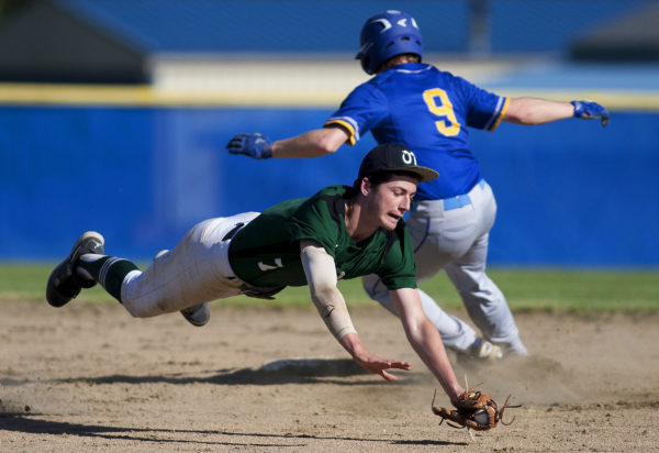Old Town's Ryan Hoogterp (left) dives to grab a wild throw to second, allowing Hermon's Matt Leach to be safe during their game in Hermon on Friday.