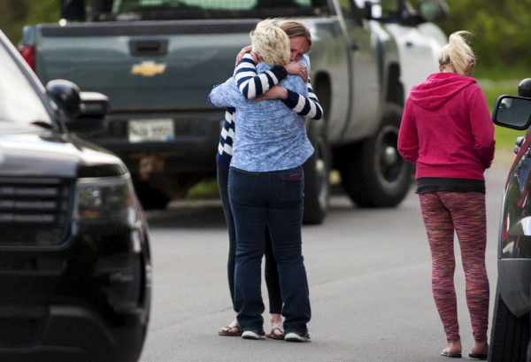 People embrace at the scene where a 1-year-old boy was fatally hit by a vehicle at Alton Elementary School Friday.