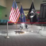 An empty chair and an accompanying display board featuring the names of Maine's prisoners of war and soldiers declared missing in action were officially installed Saturday during a ceremony at Bangor International Airport.