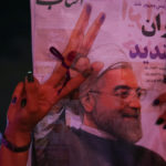 A supporter of Iranian president Hassan Rouhani holds his poster as she celebrates his victory in the presidential election, in Tehran, Iran, May 20, 2017.