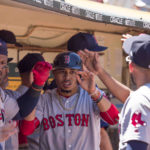 Boston's Mookie Betts gets high fives from teammates after scoring during the fifth inning against the Oakland Athletics at Oakland Coliseum on Sunday.