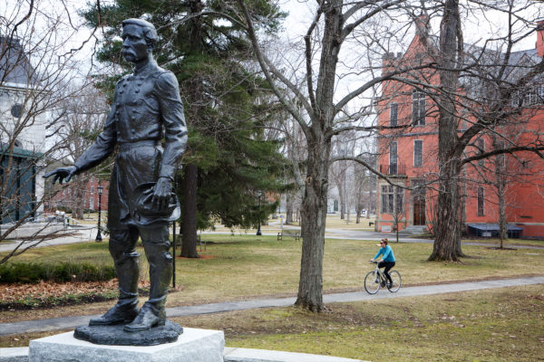 A woman cycles by the statue of Joshua Chamberlain in front of the Bowdoin College campus in Brunswick.
