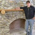 William Ellis, an instructor with a professional engineering background, stands in front of a fireplace he designed and built at the Maine School of Masonry.
