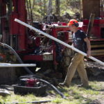 LINCOLN, Maine -- 05/16/2017 - Chris Palmer Clayton Glidden (right) brings a PVC pipe for a test well in position for Chris Palmer, both of East Coast Exploration and Drilling, in Lincoln Tuesday. The pair are contracted by Poland Springs to dig test wells for the bottling plant Poland Springs might build here. Ashley L. Conti | BDN