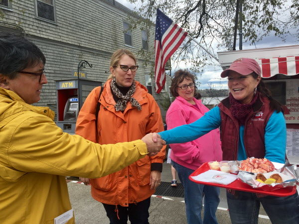 Deborah Gagnon, owner of Red's Eats, greets tourists from Ohio with a lobster roll on Wednesday. Despite paying top dollar for the loaded lobster roll, Tony and Jan Braida say &quotit's well worth it.&quot