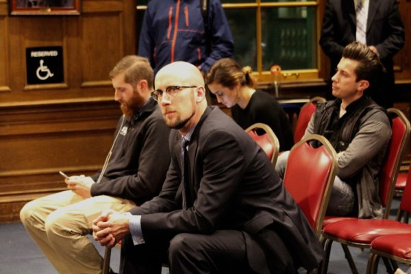 Jason Shedlock listens Monday night as Portland city councilors debate eliminating his job as assistant to Mayor Ethan Strimling.
